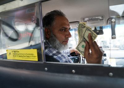 Hassan Iqbal in his cab where he works seven days a week.