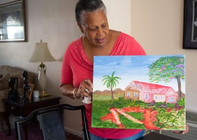 Patricia Williams shows off a painting she made of Grenada.